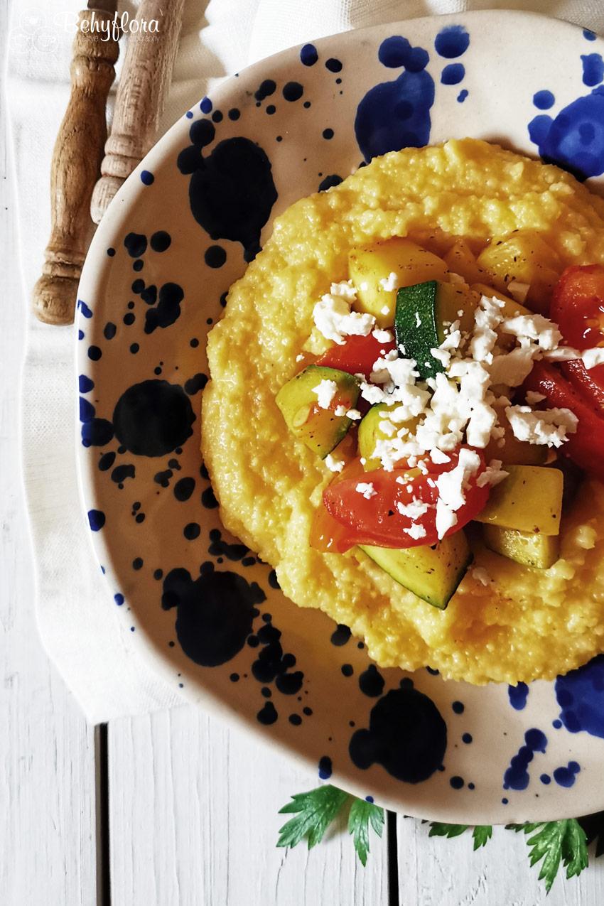 Teller mit Polenta und gebratenen Zucchini mit Tomaten und Feta